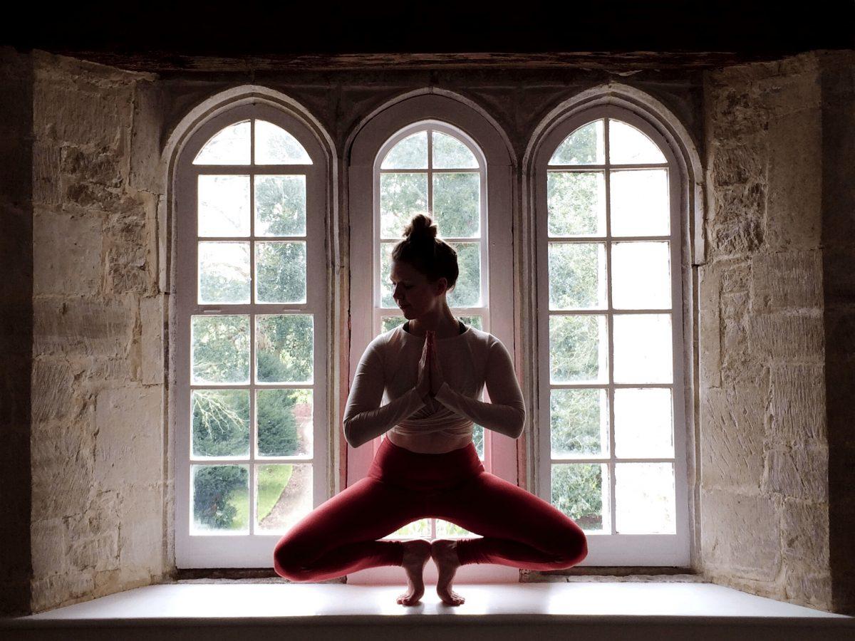 SajaRut Yoga teacher Sæunn in a toestand pose in a rustic window