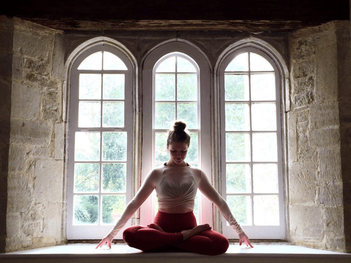 SajaRut Yoga teacher Sæunn in a lotus pose in a rustic window